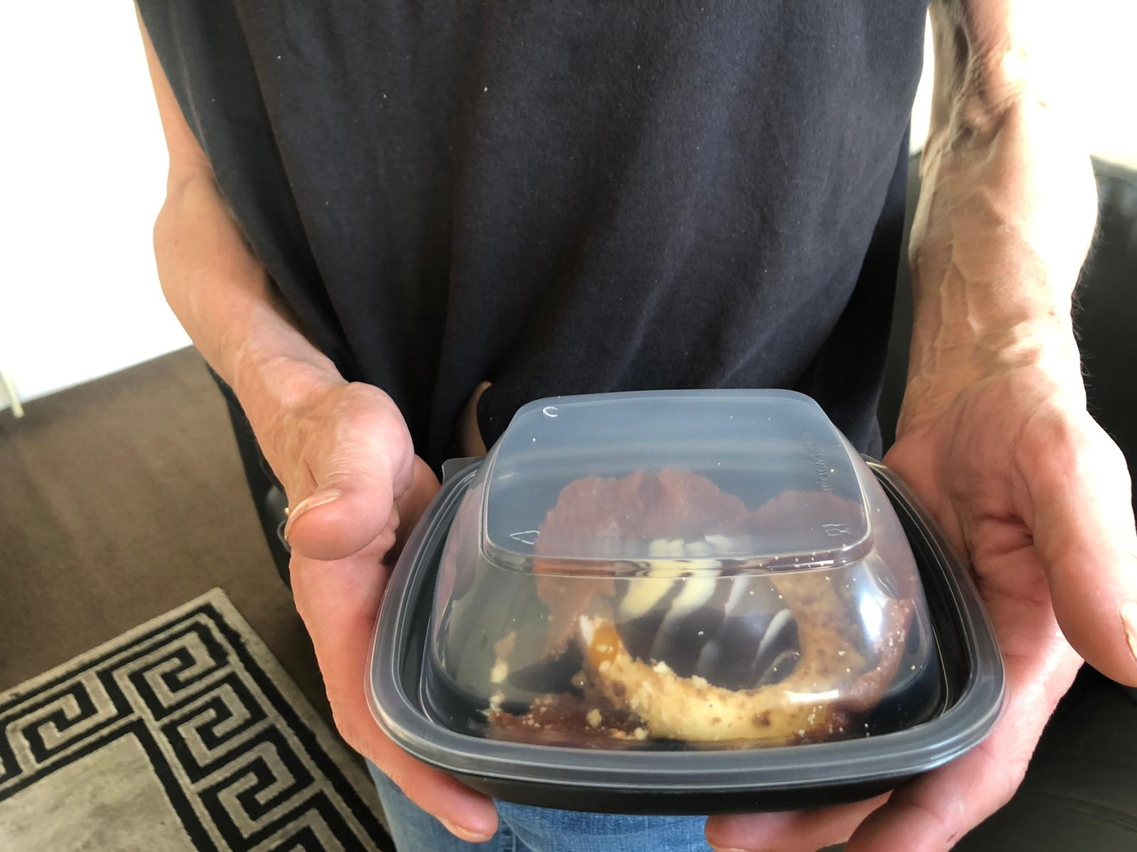One of our clients holding the Tattu Easter dessert they donated to Simon on the Streets