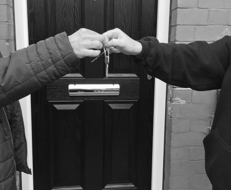 Two hands meet as keys are handed over.