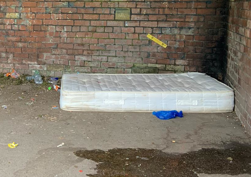 A mattress sits on the ground next to a brick wall. Rubbish is scatter around and puddle can be see in the forefront.